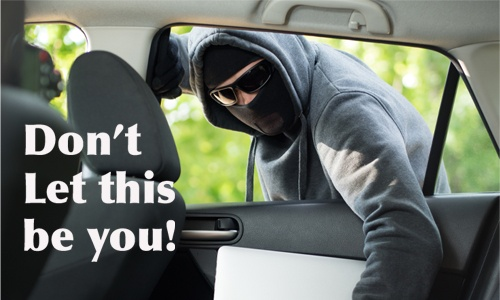 image of a thief breaking into a car and stealing the computer in the back seat